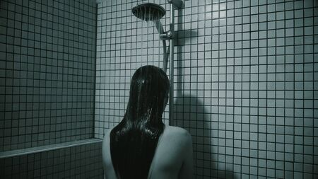 Black and white video of woman with long hairs taking a shower. She is standing by face to wall in bathroom. Depressive mood and solitude state.