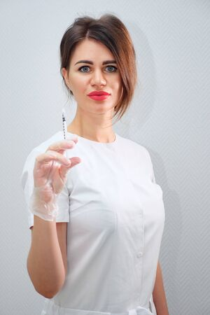 attractive woman cosmetologist with plump red lips stands and holds up syringe filled with hyaluronic acid