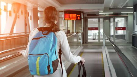 Young woman traveller on escalator with backpack and suitcase in airport terminal, sunlight. She is going to to the airport exit, copy space. Stockfoto