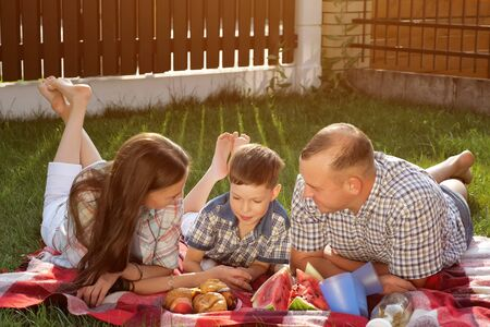 happy family members lie on stomach on red blanket and enjoy picnic in green yard on summer day close view Stock fotó