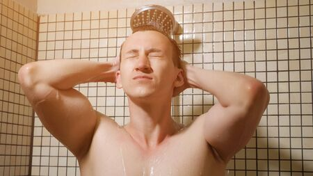 Portrait of handsome man taking a shower with rainwater showerhead in the morning. He is combing his hairs with hands standing under the water. Stock fotó