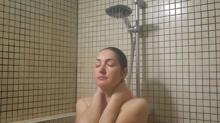 Young woman brunette is taking a warm shower in slow motion. Portrait of girl enjoying her morning routine in shower with close eyes. Stock fotó