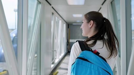 Happy young woman with backpack is going on telescopic gangway to the airplane, copyspace