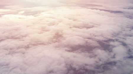 Aerial view from the plane of white soft fluffy clouds over the green landscape in sky in sunny day. Earth under the clouds in the sunlight.