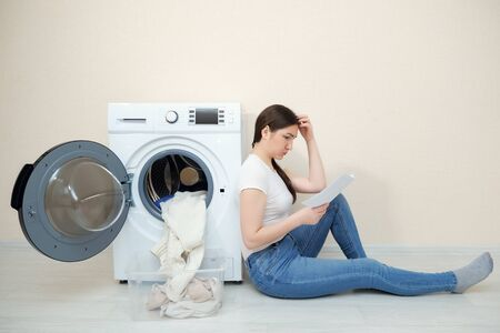 upset woman with dirty laundry in box and manual in hands sits on floor by modern washing machine in room Stockfoto