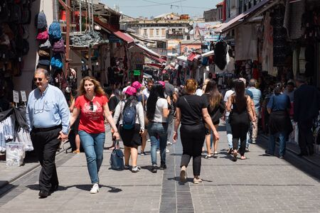 ISTANBUL, TURKEY - JULY 30 2019: Crowd of tourists and locals walks past different shops on Istanbul pedestrian street under clear blue sky on sunny day