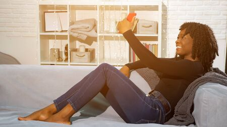 beautiful young black woman in dark pullover and jeans smiles and makes selfie sitting on grey sofa at home Stock fotó