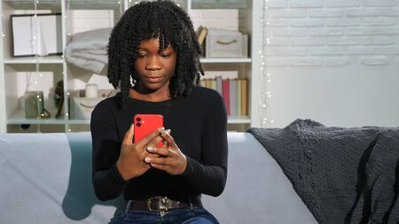 addicted to social media Afro American lady with curly hair types on modern red smartphone sitting on grey sofa in room Stock fotó