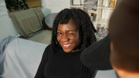 attractive young black woman with curly hair looks smiling cheerfully and slyly sitting on grey sofa closeup