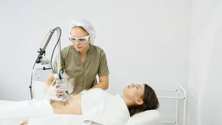 professional therapist makes laser hair removal procedure on attractive lady belly in medical beauty clinic