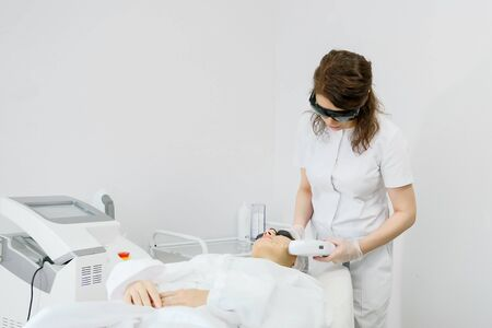 skilled therapist in white coat and black sunglasses makes laser hair removal on beauty salon patient face copy space Stock fotó