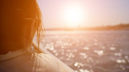 brunette woman enjoys seascape traveling by boat in sea shimmering under sun rays close-up, selective focus Stock fotó
