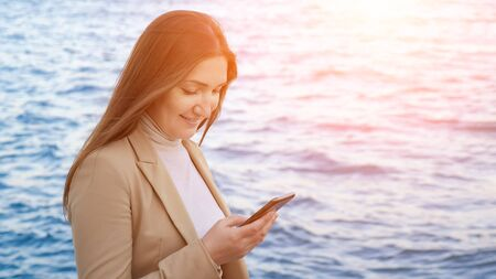 pretty girl with waving in long hair stands on beach chatting with friends on gadget against blue sea closeup