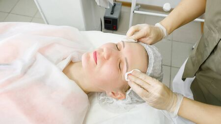 beauty salon therapist in white sterile gloves rinses patient face after laser hair removal close view Stock fotó