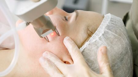 skilled beauty salon therapist in sterile gloves makes laser hair removal procedure on patient face extreme closeup Stock fotó