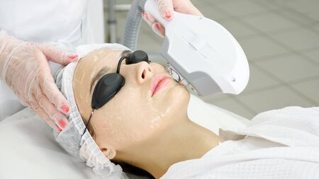 beauty salon therapist in sterile gloves removes hair on young woman forehead with laser device extreme close-up