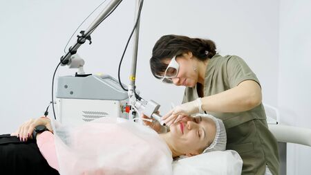 smiling brunette employee in special sunglasses removes hair from young woman face with laser device in beauty salon