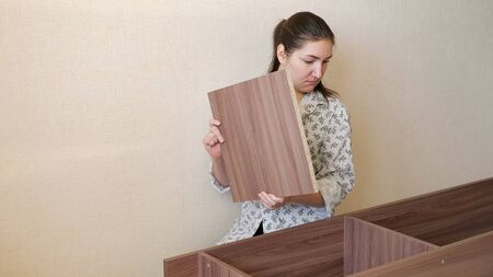 brunette girl in home clothes sits on kitchen floor and tries to assemble prefabricated wooden cupboard parts Stock fotó