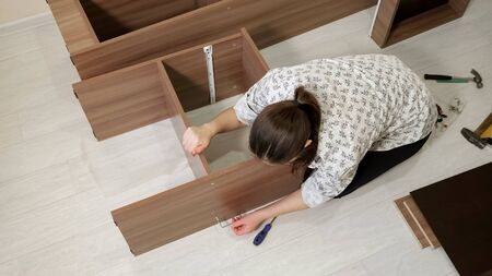 woman with dark hair sits on floor and assembles new prefabricated cabinet rotating tool to connect shelf parts upper view