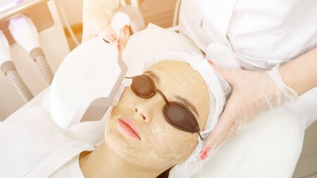 young woman patient in special black glasses lies on white couch and beauty salon therapist makes laser epilation sunlight