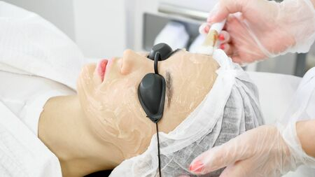 professional therapist spreads special ointment on beauty salon woman client face before laser epilation side view Stock fotó