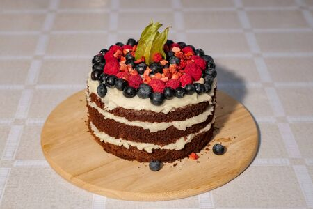 cake is decorated with fresh strawberries and blueberries on the table.