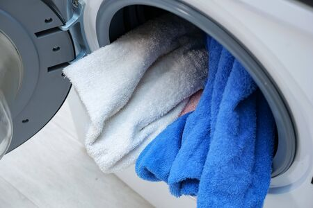 modern washing machine with heap of laundry in drum and open door top view