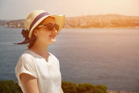 young woman in a hat and glasses on the background of the sea., sunlight