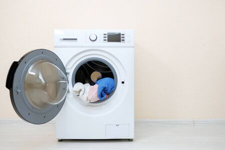 modern washing machine with heap of laundry in drum and open door stands on wooden floor near beige wall