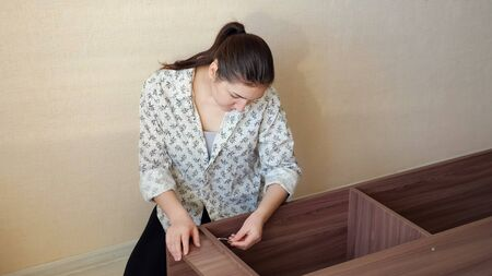 brunette girl in home clothes sits on kitchen floor and tries to assemble prefabricated wooden cupboard parts closeup 写真素材