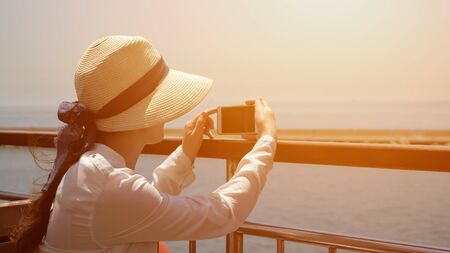 lady in elegant straw hat sits on ship deck and makes video of beautiful seascape sailing past pier on shiny day closeup Stock fotó