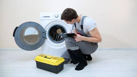 skilled repairman writes on clipboard checking broken washing machine on floor in room closeup Stock fotó