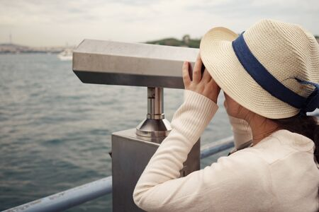 Brunette woman in white sweater and hat looks through binoculars exploring cityscape closeup