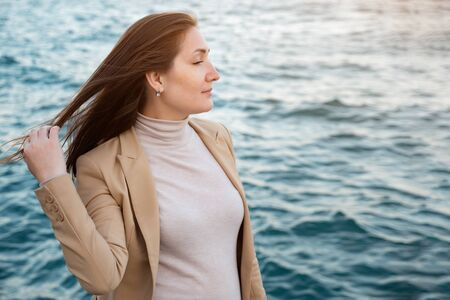 cheerful woman touches long hair standing on waterfront enjoying beautiful nature against rippling sea copy space
