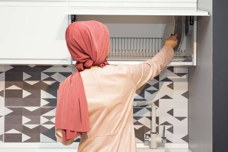 muslim woman in hijab opens kitchen cabinet on modern kitchen back view