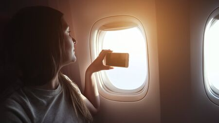 young happy girl makes video on phone aircraft passenger cabin window close-up