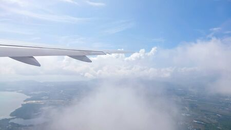 wing of airplane flying through clouds over receding land with towns rivers mountains against sky with white clouds