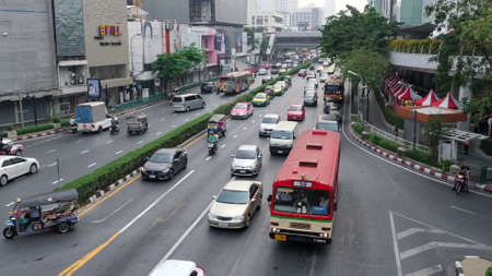 BANGKOK/THAILAND - FEBRUARY 15 2020: Wide asphalt downtown street road with cars driving in traffic past green trees cafes and modern business highrise buildings upper view on February 15 in Bangkok Editorial