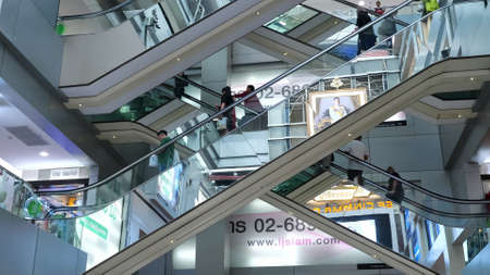 BANGKOK/THAILAND - FEBRUARY 15 2020: Breathtaking city multi-level shopping mall with glass escalators between grey floors and people traveling against bright signboards on February 15 in Bangkok Editorial
