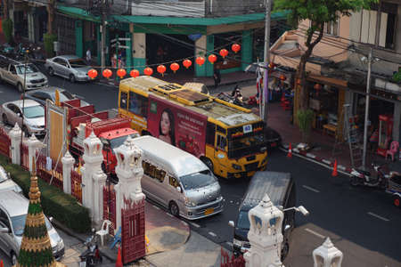 BANGKOK/THAILAND - FEBRUARY 15 2020: Traditional red lanterns over narrow asphalt street road with cars driving in traffic jam among old buildings upper view slow motion on February 15 in Bangkok