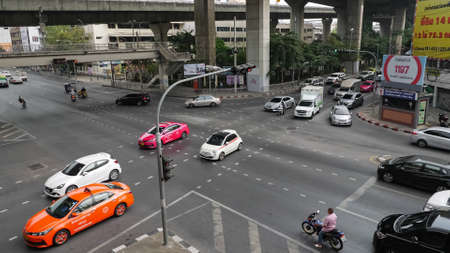 BANGKOK/THAILAND - FEBRUARY 15 2020: Wide asphalt downtown street road with cars and traffic lights upper view on February 15 in Bangkok