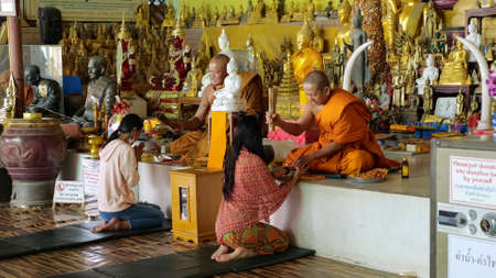 PHUKET /THAILAND - FEBRUARY 15 2020: Girl travelers sit on knees in front of Buddhist monks conducting special spiritual ritual with incense sticks against Buddha statues on February 15 in Phuket