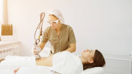 professional therapist makes laser hair removal procedure on attractive lady belly in medical beauty clinic sunlight