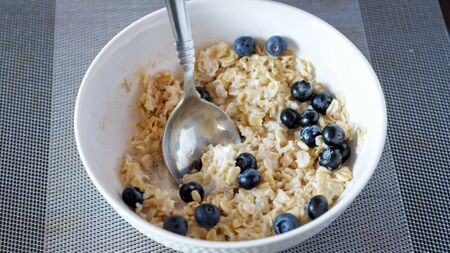 man eats delicious oatmeal cereals with blueberries and milk for breakfast at home close-up