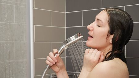 joyful young woman with long loose wet hair sings into silver shower sprinkler dancing in tiled bathroom at home closeup