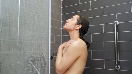 young woman with long loose wet hair stands under shower in bathroom at hotel Standard-Bild