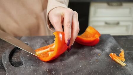 accurate woman with nice manicure cuts fresh red Bell pepper using big knife preparing salad for family closeup