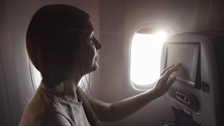 young woman with dark hair in earphones chooses music against bright porthole in airliner passenger cabin close view