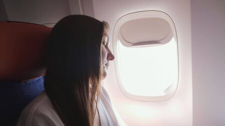pretty woman with loose brown hair in grey t-shirt tries to sleep against bright airliner window in passenger cabin closeup