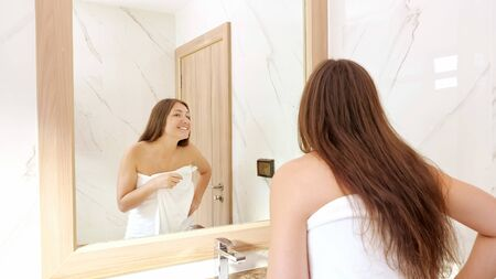 young woman brushes teeth with white toothbrush and looks at reflection in bathroom mirror with smile close view